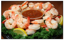 An array of cooked shrimp around a bowl of cocktail sauce; fresh and frozen shrimp can be bought by the pound in Western MA at The Other Brother Darryl's, which sells fish, seafood, and shellfish galore.